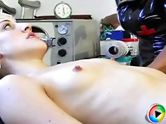 Nurse Maxine ties her patient to the table and teases her with several toys