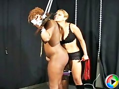 Maxine gets Dahlia chained in the stocks and lashes her with the whip