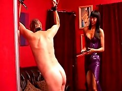 Asian lady in latex dress trains old male slave pinning his nuts and whipping his back and ass cheeks