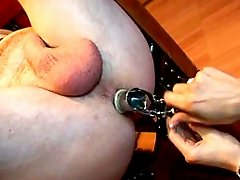 Sexy strapon domina penetrates male slave`s ass with speculum then strapon fucks him